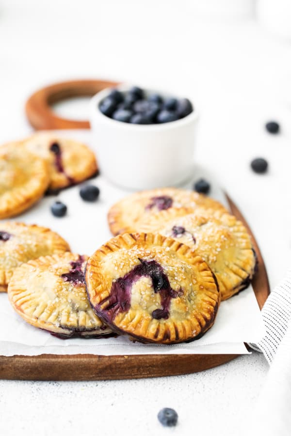 Easy Blueberry Hand Pies on a wooden serving platter sprinkled with coarse sanding sugar.