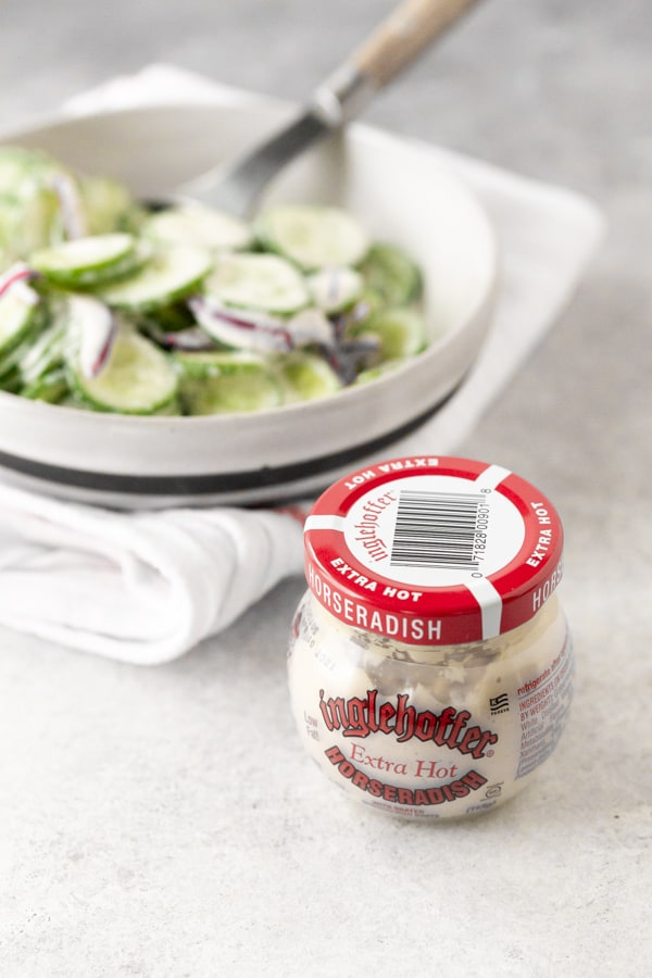 a jar of horseradish sauce sitting in front of a bowl of creamy horseradish cucumber salad.