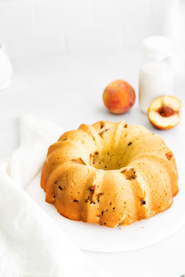 Peach Bundt Cake on a cake plate with some fresh peaches in the background.