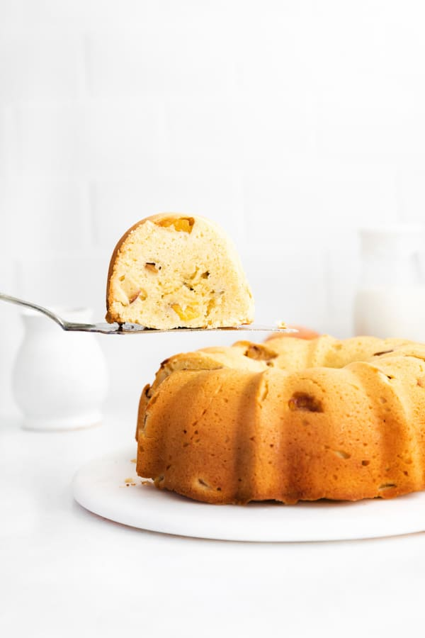 Peach Bundt Cake with a sliced being lifted out of the cake.