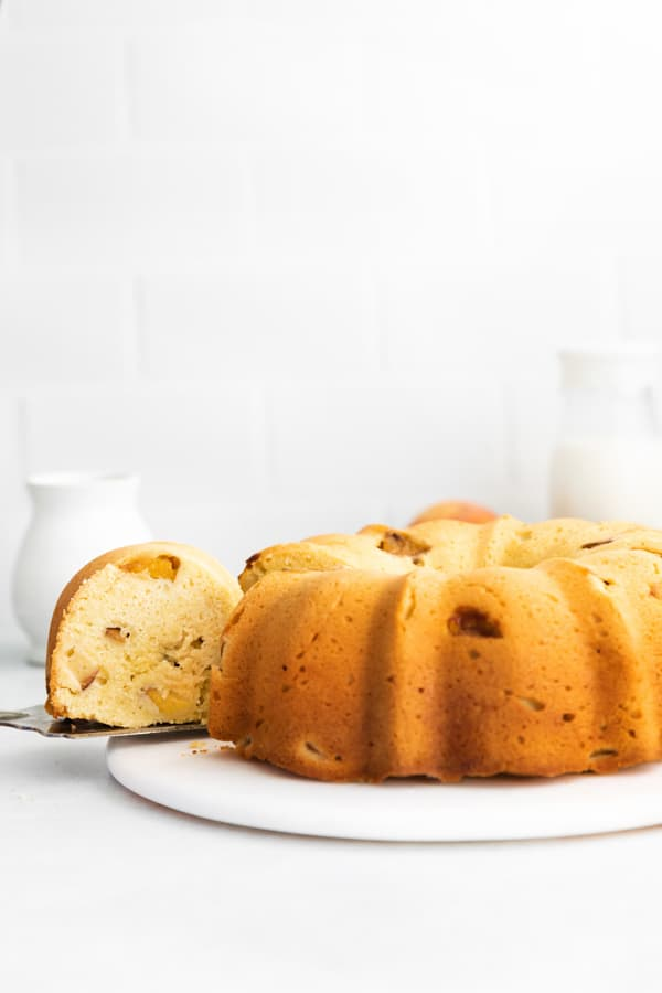 Peach Bundt Cake with a slice being take out of the cake.