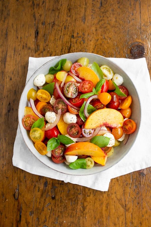 Tomato Peach Caprese Salad in a bowl sitting on a white napkin.