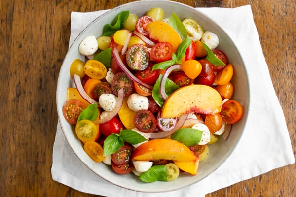Tomato Peach Caprese Salad in a bowl sitting on a wood table.