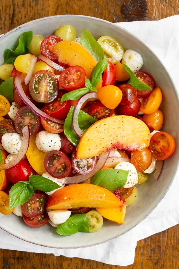 tomato peach Caprese salad in a bowl.