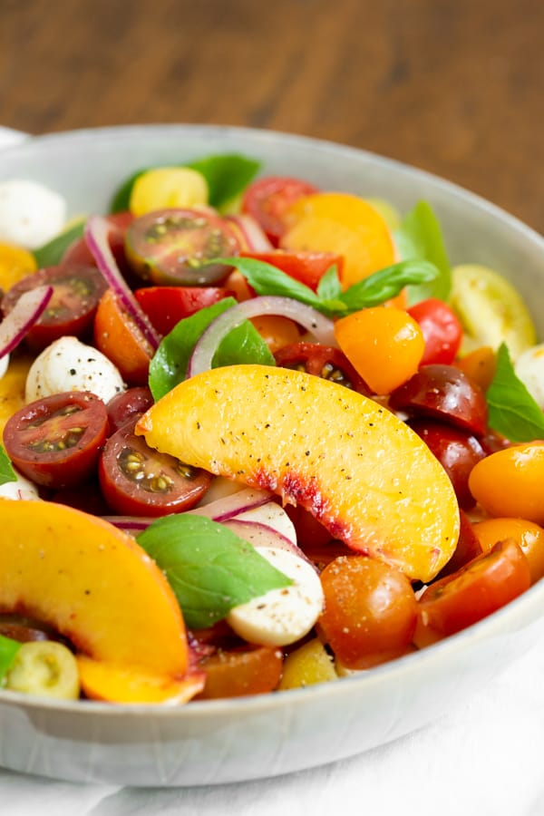 Tomato Peach Caprese Salad in a bowl with fresh basil.