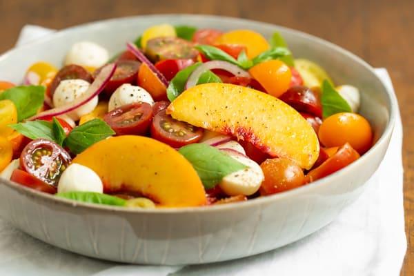 Tomato Peach Caprese Salad served in a grey bowl.