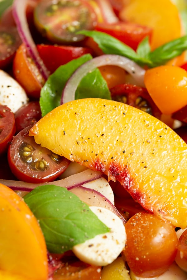 close up pictures of a sliced peach in a Tomato Peach Caprese Salad.