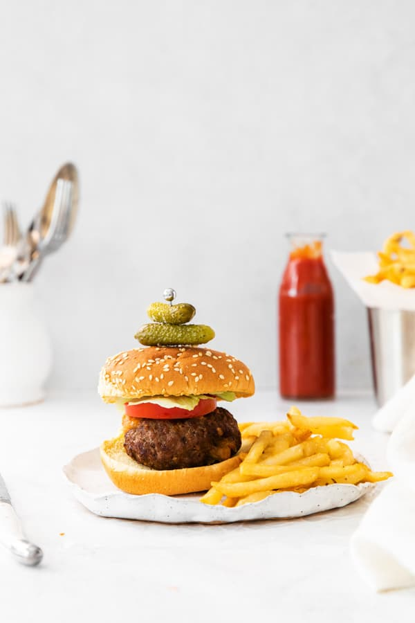 air fryer Juicy Lucy burger on a serving plate with french fries.
