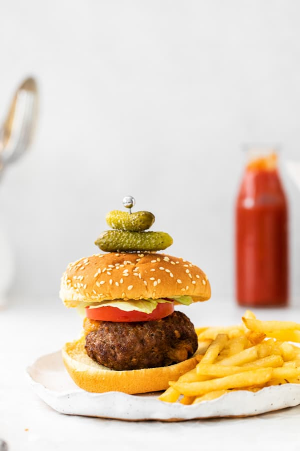 air fryer Juicy Lucy burger sitting on a plate with 2 pickles stuck to the top of the bun.