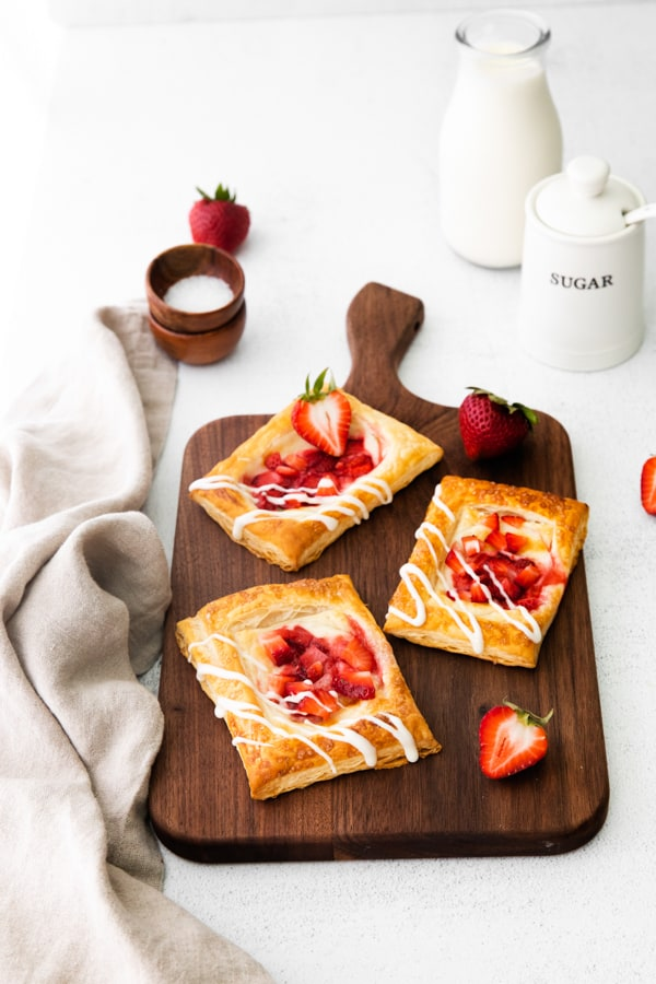 easy strawberry cheesecake Danish served on a cutting board with fresh berries.