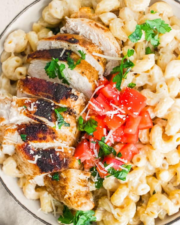 Instant Pot Cajun Chicken Alfredo topped with parsley and fresh diced tomatoes.