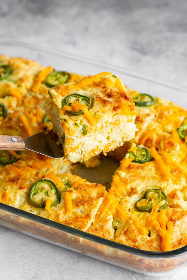 a piece of jalapeño cheddar cornbread being taken out of a 9x13 tray.