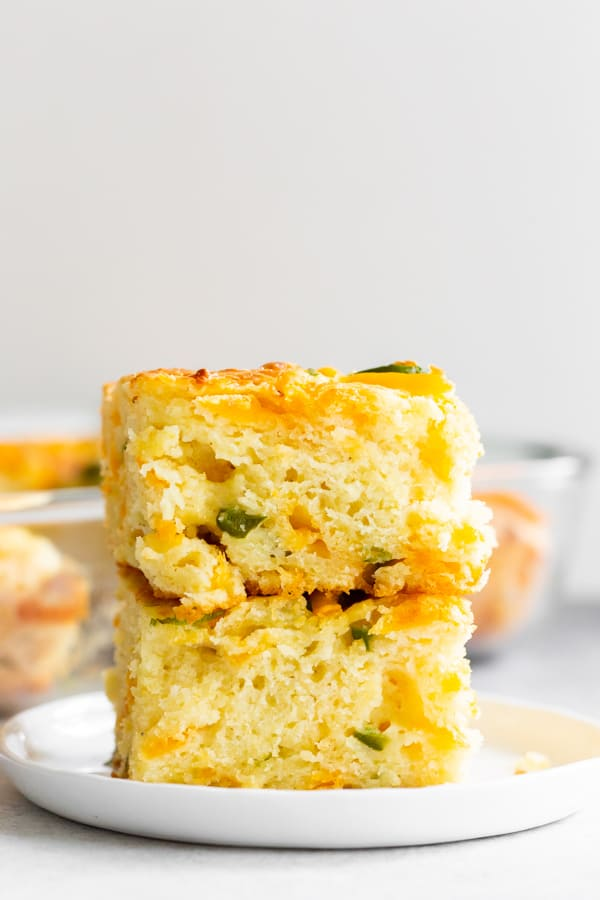 2 pieces of jalapeño cheddar cornbread stacked on a plate.