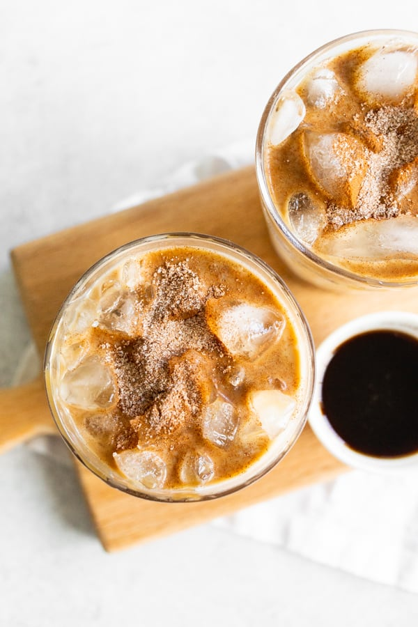 Apple Crisp Macchiato in a glass with ice and topped with cinnamon sugar and caramel drizzle.