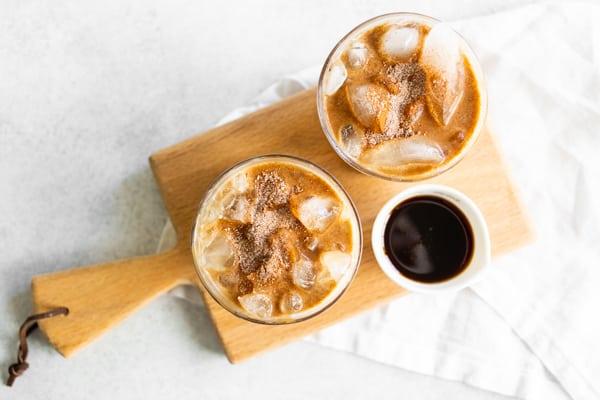 Apple Crisp Macchiato coffee drinks sitting on a mini wooden cutting board.