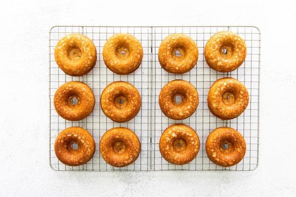 Baked apple cider donuts sitting on a cooling rack.