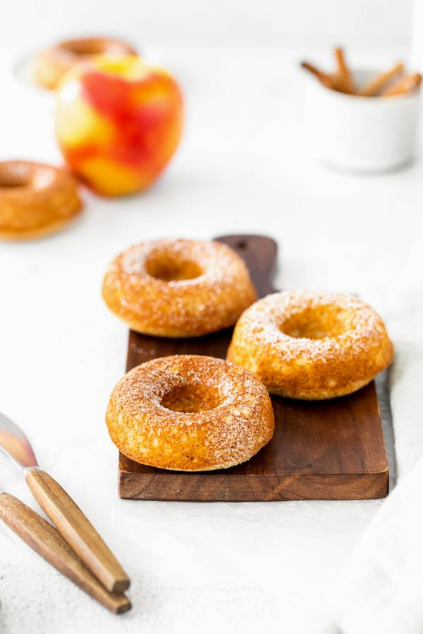 Baked apple cider donuts sitting on a cutting board and topped with cinnamon sugar.