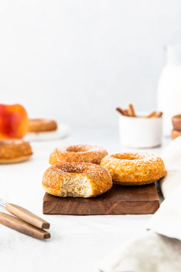 A Baked apple cider donut sitting on a serving board with a bite take out of the donut.