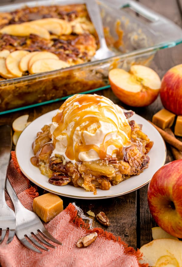 Caramel Apple Dump Cake topped with ice cream with caramel.