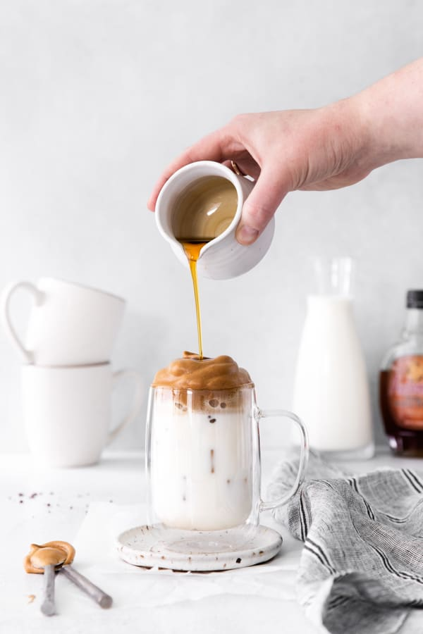 Pouring maple syrup onto their Maple Whipped Coffee.