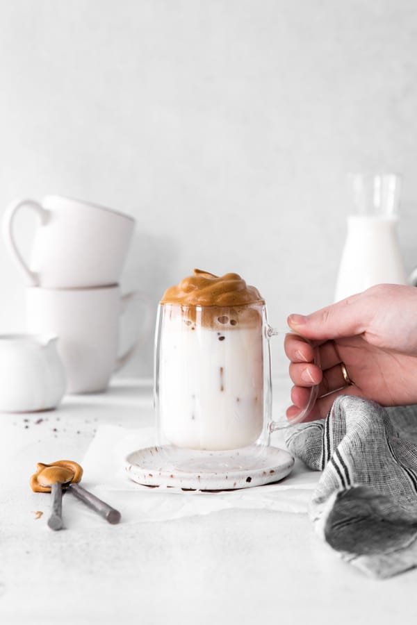 A hand holding a glass of Maple Whipped Coffee.
