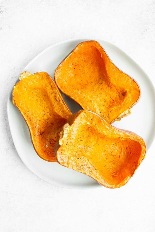roasted honeynut squash sitting on a white plate.