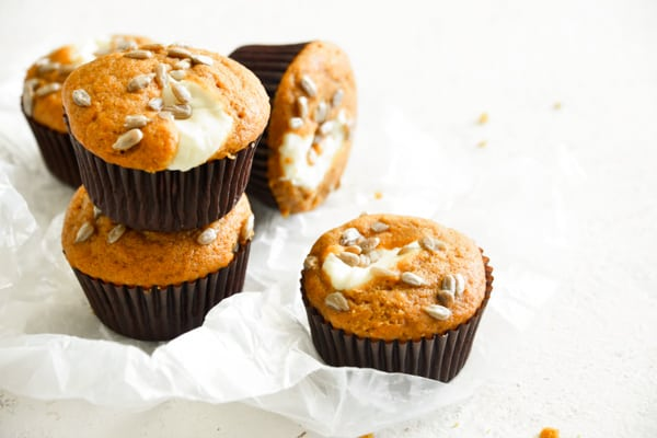 Pumpkin Cream Cheese Muffins stacked on a white board.
